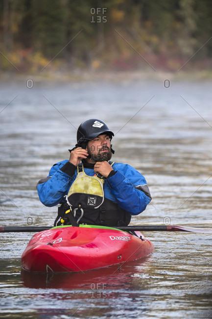 Jackson Hole, WY, USA - September 20, 2016: Bearded man putting on helmet while kayaking on Snake River, Jackson Hole, Wyoming, USA