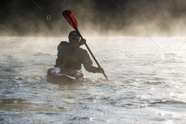 Jackson Hole, WY, USA - September 20, 2016: Front view of kayaker paddling on foggy Snake River, Jackson Hole, Wyoming, USA