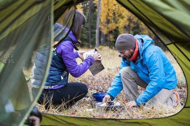 Jackson, Wyoming, USA - September 22, 2016: Couple setting up camping stove near tent entrance, Jackson, Wyoming, USA