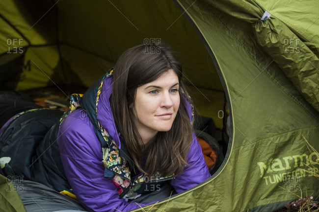 Jackson, Wyoming, USA - September 22, 2016: Female camper looking out of tent, Jackson, Wyoming, USA