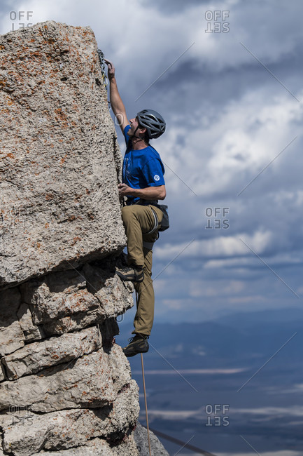 Jackson Hole, Wyoming, USA - September 19, 2016: Male climber clipping rope to final anchor after reaching summit of rock, Jackson Hole, Wyoming, USA