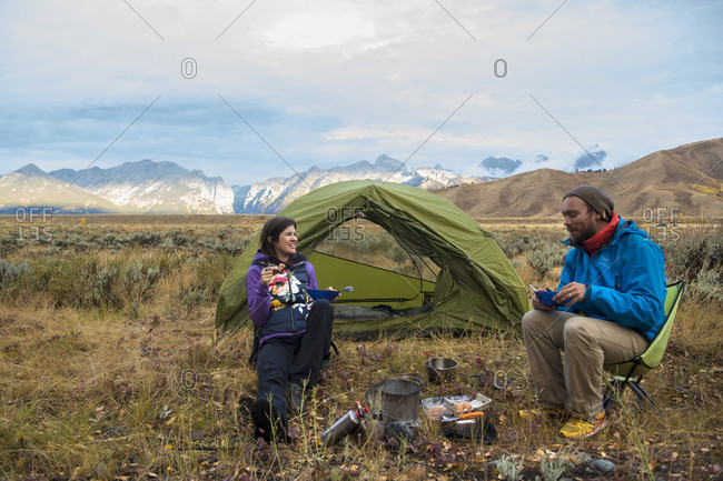 Jackson, Wyoming, USA - September 22, 2016: Couple eating while camping in front of tent, Jackson, Wyoming, USA