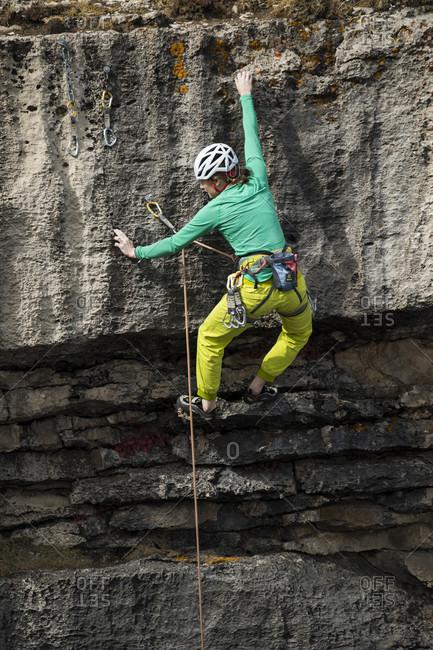 Jackson Hole, Wyoming, USA - September 19, 2016: Female climber reaching for handholds on rock face, Jackson Hole, Wyoming, USA