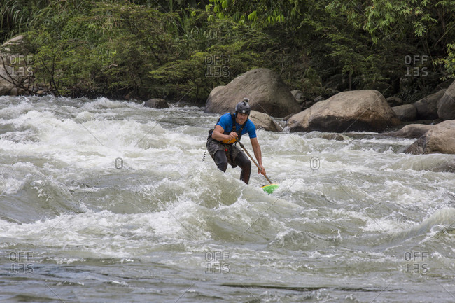 Manu National Park, Peru, Peru - May 5, 2017: Man rides wave in jungle of Peru on stand-up paddleboard (SUP) while on river expedition in the Peruvian Amazon