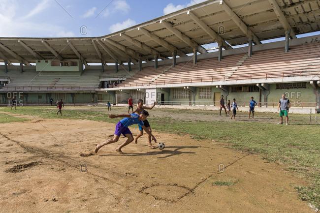 Baracoa, Baracoa, Cuba - March 18, 2017: Group of boys playing football at stadium, Baracoa, Cuba