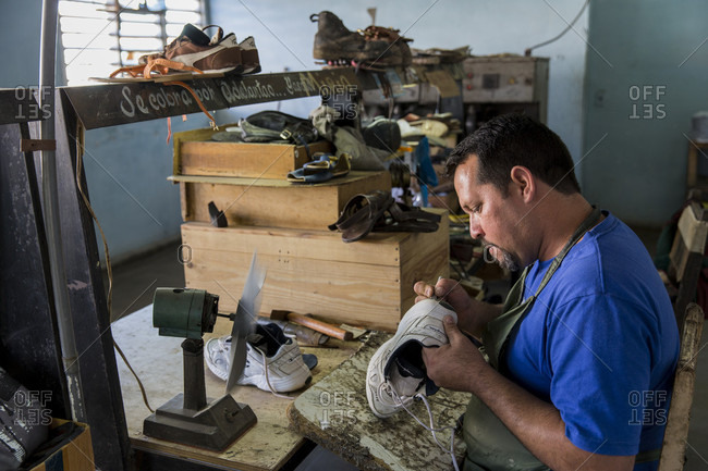 La Palma, La Palma, Cuba - March 10, 2017: Male shoemaker repairing shoe in workshop, La Palma, Cuba