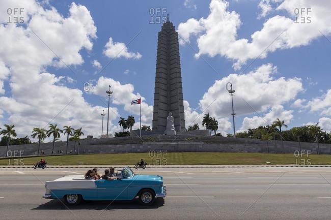 Havana, Havana, Cuba - March 19, 2017: Tourists driving vintage car at Plaza de la Revolucion with Jose Marti Memorial in background, Havana, Cuba