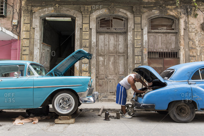 Havana, Havana, Cuba - March 20, 2017: Man fixing car in street of Havana, Cuba