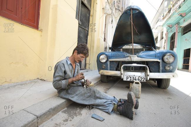 Havana, Havana, Cuba - May 11, 2015: Man fixing car in street of Havana, Cuba