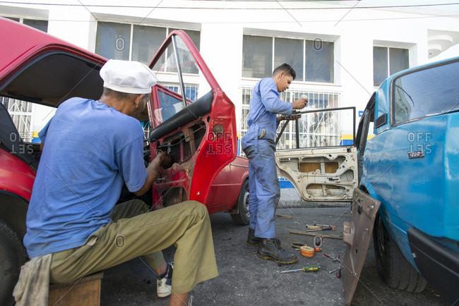 Havana, Havana, Cuba - May 12, 2015: Auto mechanics fixing cars in street of Havana, Cuba