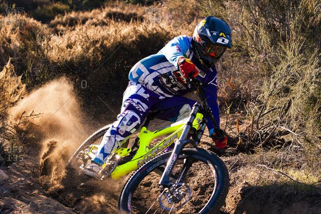 Southern California , California, USA - December 1, 2011: Downhill biker turns through a dusty berm