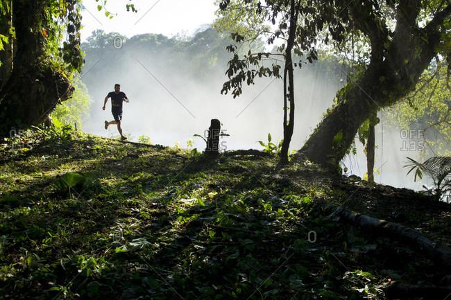 Agua Azul, Chiapas, Mexico - May 12, 2014: Man running in natural scenery, Agua Azul, Chiapas, Mexico