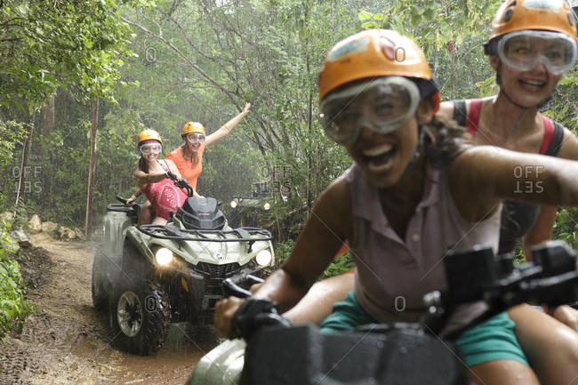 Emotions Park, Quintana Roo, Mexico - November 24, 2015: Women laughing while driving quad bikes in Emotions Native Park during rain, Quintana Roo, Mexico