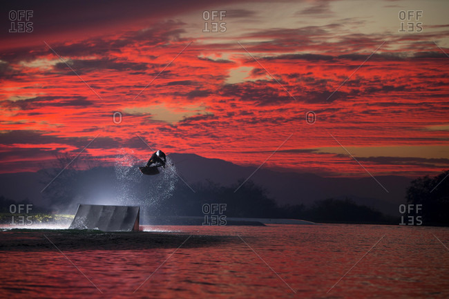 Tequesquitengo, Morelos, Mexico - January 21, 2016: Wakeboarder performing jump against dramatic red sky at dusk, Tequesquitengo, Morelos, Mexico