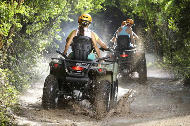 Emotions Park, Quintana Roo, Mexico - November 24, 2015: Rear view of couples driving quad bikes through dirt road puddles in Emotions Native Park, Quintana Roo, Mexico