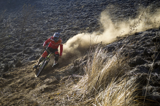 Tenango, State of Mexico, Mexico - April 2, 2016: Front view of biker raising dust on downhill track, Tenango, State of Mexico, Mexico