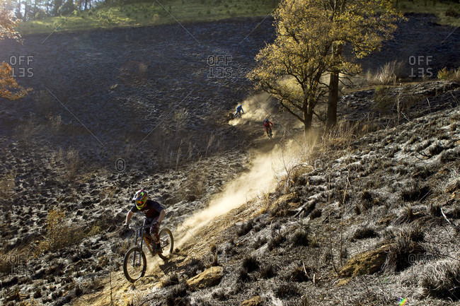 Tenango, State of Mexico, Mexico - April 2, 2016: Side view of biker crossing downhill track and raising dust, Tenango, State of Mexico, Mexico