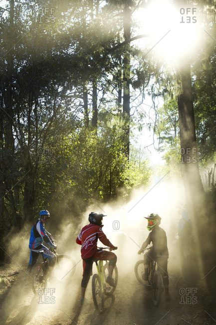 Tenango, State of Mexico, Mexico - April 2, 2016: Rear view of bikers waiting in dust for flock of sheep to pass, Tenango, State of Mexico, Mexico