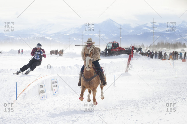Jackson Hole, WY, United States - February 1, 2016: Skier races behind galloping horse at annual Skijoring competition held at Jackson Hole Mountain Resort, Teton Village, Wyoming, USA
