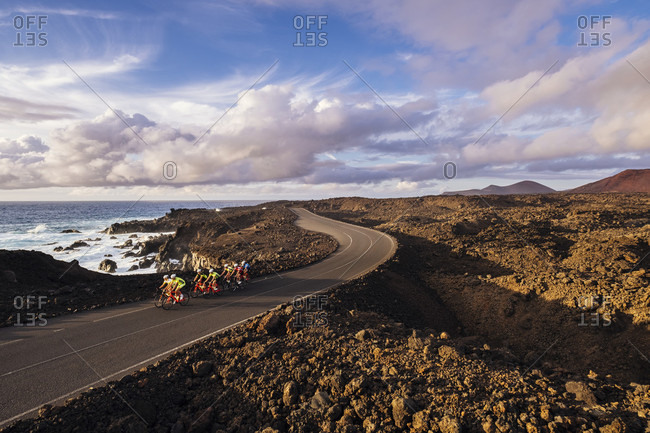 Timanfaya, Lanzarote, Spain - October 22, 2016: Group of cyclists pedaling on coastal road, Timanfaya National Park, Lanzarote, Canary Islands, Spain