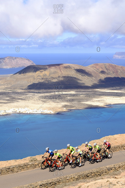 Lanzarote, Canary Islands, Spain - October 22, 2016: Group of cyclists pedaling on coastal road, Timanfaya National Park, Lanzarote, Canary Islands, Spain