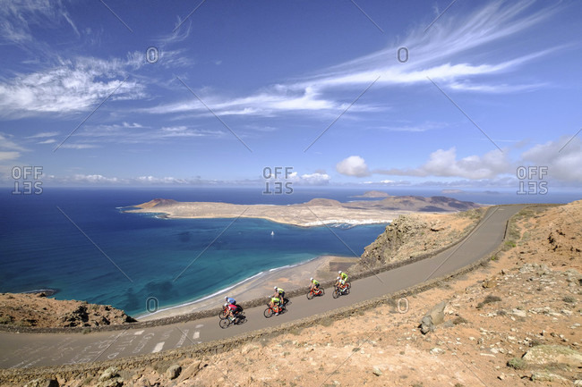 Lanzarote, Canary Islands, Spain - October 22, 2016: Group of cyclists pedaling on coastal road, Lanzarote, Canary Islands, Spain