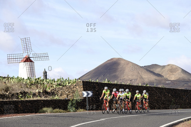 Lanzarote, Canary Islands, Spain - October 22, 2016: Group of cyclists pedaling on road with volcanoes and windmill in background, Lanzarote, Canary Islands, Spain