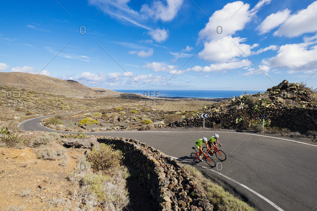 Lanzarote, Canary Islands, Spain - October 22, 2016: Road cyclists riding side by side on road, Lanzarote, Canary Islands, Spain