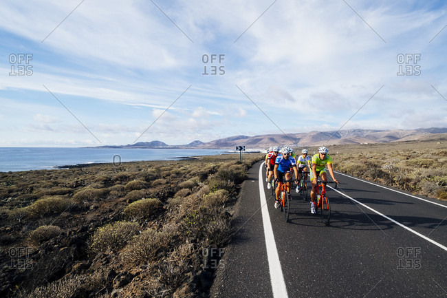 Lanzarote, Canary Islands, Spain - October 22, 2016: Group of road cyclists riding on road near coastline, Lanzarote, Canary Islands, Spain