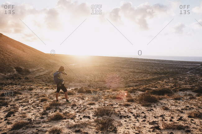 Tenerife, Spain - July 5, 2017: Woman photographing scenery with sand dunes at sunset, Tenerife, Canary Islands, Spain