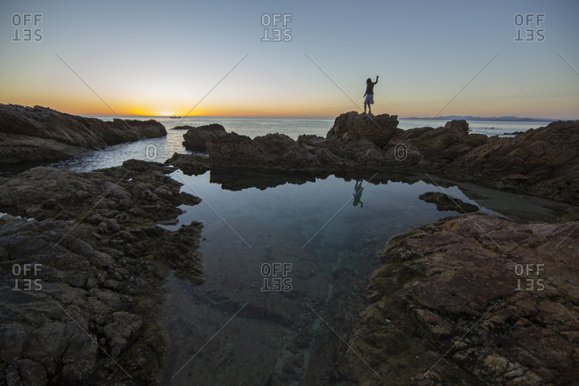 Lanzarote, Canary Islands, Spain - March 11, 2016: Adult woman standing on a rock outcrop overlooking the sea at sunrise