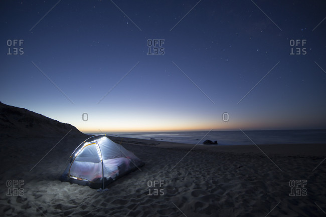 A lone tent pitched on a remote beach at twilight