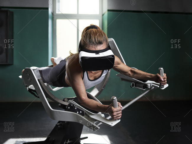 Woman wearing VR glasses using futuristic fitness machine
