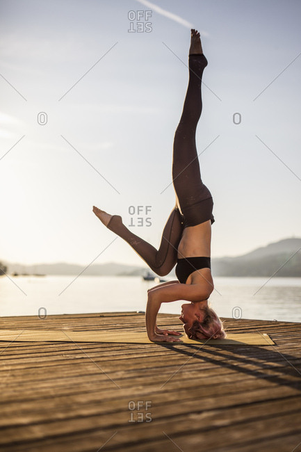 Woman practicing yoga on jetty at a lake doing a headstand