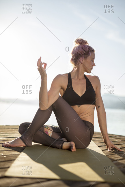 Woman sitting on jetty at a lake practicing yoga
