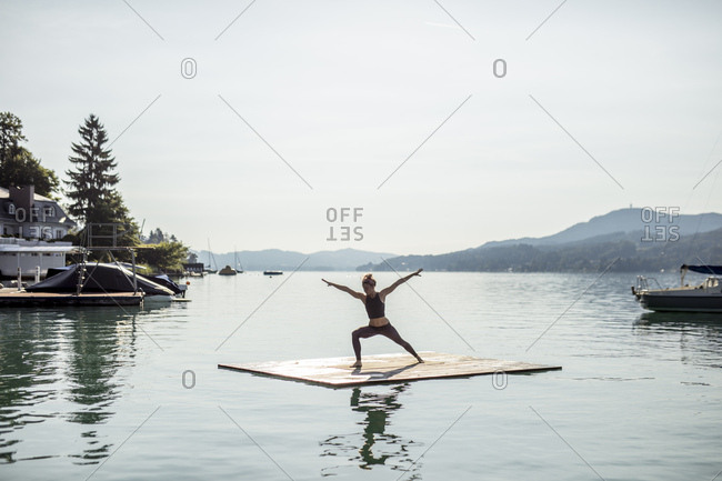 Woman practicing yoga on raft in a lake