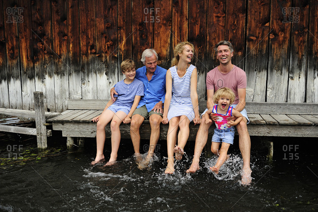 Family sitting together on jetty splashing with water