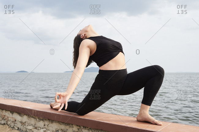Young woman practicing yoga on a wall by the sea