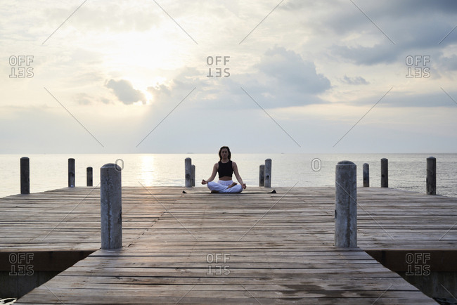 Young woman practicing yoga on a jetty by the sea at sunset