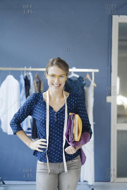 Portrait of laughing fashion designer in her studio