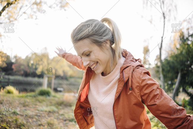 Portrait of happy young woman balancing in autumnal park