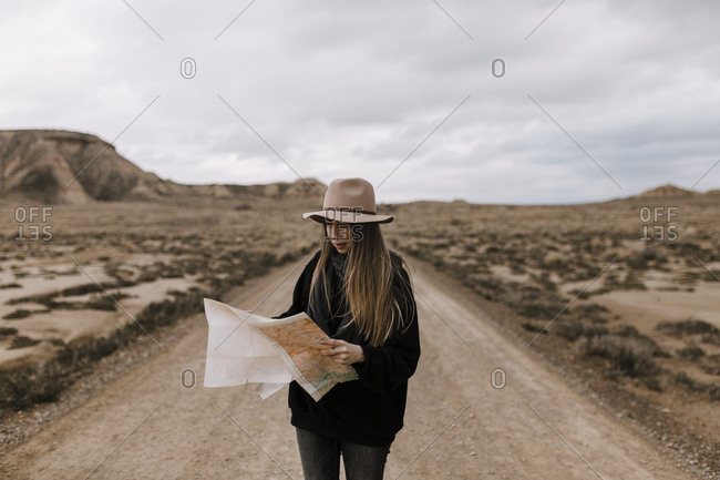 Woman with map standing on dirt road in barren landscape