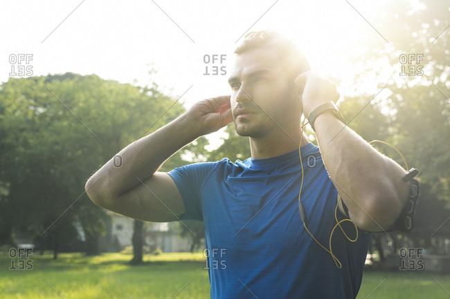 Sportive man wearing headphones- preparing for training in urban park