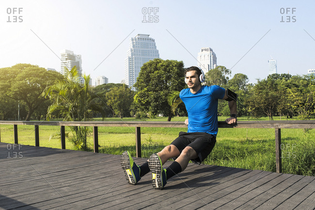 Runner with headphones doing push-ups in urban park