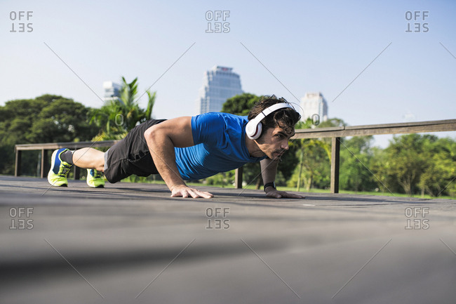 Athlete exercising push-ups in the city