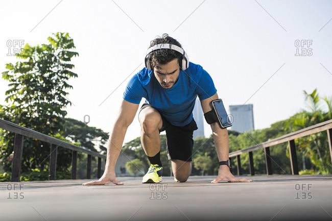 Runner training start position on street in urban park- wearing headphones