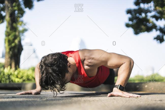 Athlete doing push-ups in urban park