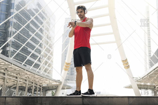 Athlete with earphones checking his smartwatch