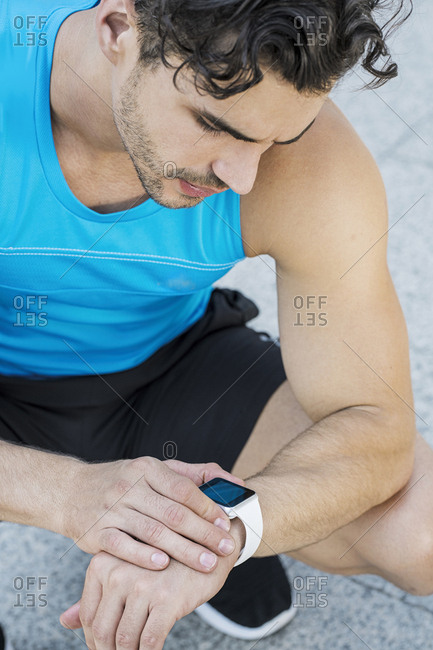Athlete sitting on the ground- checking his smartwatch