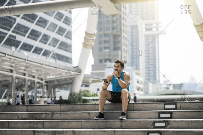 Runner wearing earphones- checking messages on his smartphone